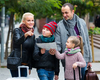 Parents with two kids and baggage with map Stock Images