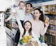 Parents with two kids buying fruit yoghurt Stock Images