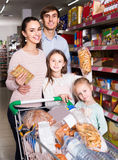 Parents with two kids choosing biscuits in store Royalty Free Stock Photography