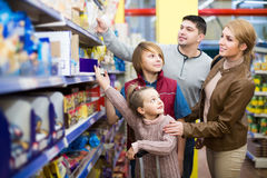 Parents with two kids choosing crispy flakes in shop Stock Image
