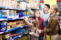 Parents with two kids choosing crispy flakes in shop Royalty Free Stock Photo