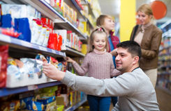 Parents with two kids choosing groats in food store Royalty Free Stock Image