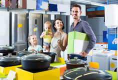 Parents with two kids choosing kitchenware in home appliance sto. Cheerful russian parents with two kids choosing kitchenware in home appliance store stock photography