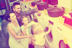 Parents with two kids choosing washing machine in home appliance Royalty Free Stock Photography
