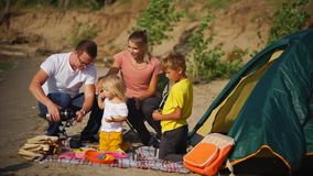 Family picnic in the countryside. Parents and two kids having a picnic near the tent during the camping holidays in the countryside stock video