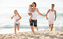 Parents with two kids jogging on beach. Joyful young active parents with two little children jogging together on sandy beach . Focus on woman Stock Photo