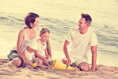 Parents with two kids playing with toys on beach. Cheerful glad smiling parents with two kids playing with sand toys on beach Royalty Free Stock Images