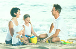 Parents with two kids playing with toys on beach. Cheerful positive  parents with two kids playing with sand toys on beach Stock Photos