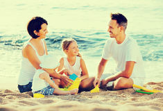 Parents with two kids playing with toys on beach. Cheerful positive smiling parents with two kids playing with sand toys on beach Royalty Free Stock Photography