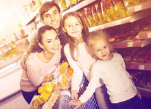 Parents with two kids and purchases in shopping cart Stock Images