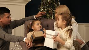 Parents and two little children having fun and playing together near Christmas tree indoors. royalty free stock images