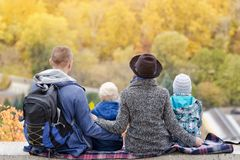 Parents and two sons look at the loess of height. Autumn. Back view.  Royalty Free Stock Images