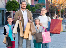 Parents with two teenagers going for shopping outdoors Stock Photos