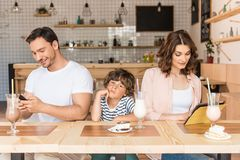 Parents using gadgets while their son bored. In cafe Stock Images