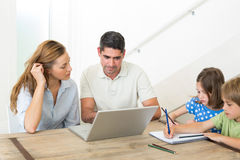 Parents using laptop while children coloring Royalty Free Stock Images