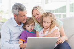 Parents using laptop with children. Parents using laptop with son and daughter at home Royalty Free Stock Photos