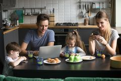 Parents using laptop and smartphones having morning breakfast wi. Parents using laptop and smartphones having breakfast with children, smiling dad reading royalty free stock photography
