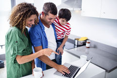 Parents using laptop with son in kitchen stock photography