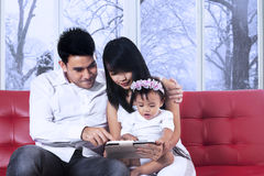 Parents using tablet with their daughter Royalty Free Stock Photography