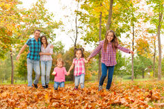 Parents walk in the park with little girls Stock Photo