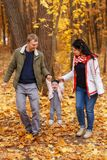 Parents walk and play with little daughter Stock Photos