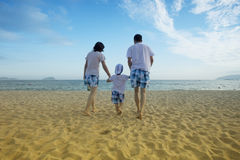 Parents walking with child on the beach Stock Images