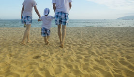 Parents walking with child on the beach Stock Photography