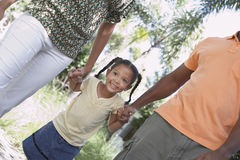 Parents Walking With Daughter In Park Stock Photo