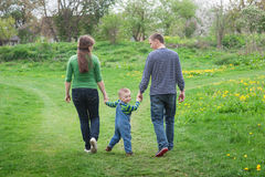 Parents are walking with a little boy on a green spring meadow on a footpath Royalty Free Stock Images
