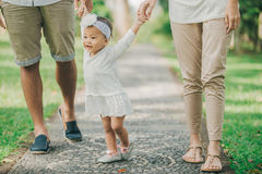 Parents walking with their baby daughter in the park Stock Images
