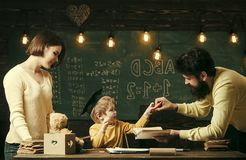 Parents wants to grow up genius son. Wunderkind and genius concept. Father, teacher reading book, teaching kid, son. Chalkboard on background. Boy child in royalty free stock photo