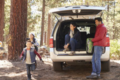Parents watch kids and prepare for hike at the back of car Royalty Free Stock Photo