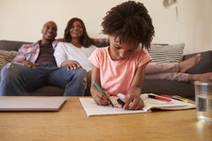 Parents Watch TV As Daughter Colors In Picture Book Stock Photography