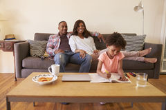 Parents Watch TV As Daughter Colors In Picture Book stock photo