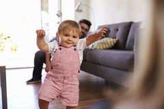 Parents Watching Baby Daughter Take First Steps At Home Stock Photo