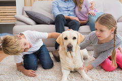 Parents watching children on rug with labrador Royalty Free Stock Image