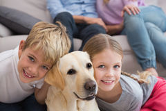 Parents watching children on rug with labrador Stock Image