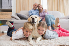Parents watching children on rug with labrador Royalty Free Stock Photography