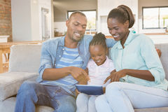 Parents watching daughter using tablet pc Royalty Free Stock Photos