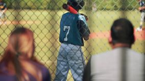 Parents watching kid at baseball game from the stands. stock footage