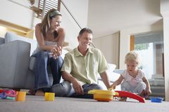 Parents Watching Son Playing With Toy Stock Photos