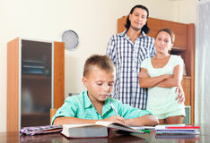 Parents watching their son doing homework Stock Photography