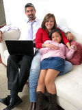 Parents whit son look on notebook and television Royalty Free Stock Images