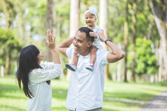 Parents in white clothes walking with their baby daughter in the royalty free stock images