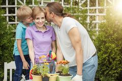 Happy family gardening together and taking care of nature. Parents and 8-year old child having fun in planting farm outdoo in spring sunny day, planting flowers Stock Photos