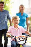 Parents with young boy on bike. Parents with young boy riding bike in city smiling at camera Royalty Free Stock Image