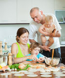Parents with young children dumplings fish cooking in a home kit Stock Photography