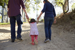Parents and young daughter walk hand in hand on a rural path Royalty Free Stock Photos