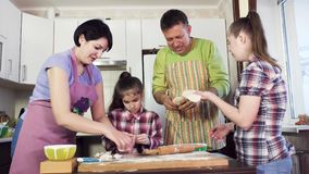 Parents and young sisters have great time and prepare meal. Parents young sisters elder is Downs girl wearing checked shirts have great time and prepare stock footage