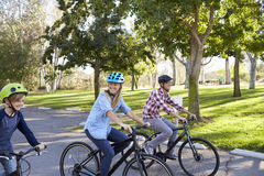 Parents and young son cycling through a park, close up Stock Photos